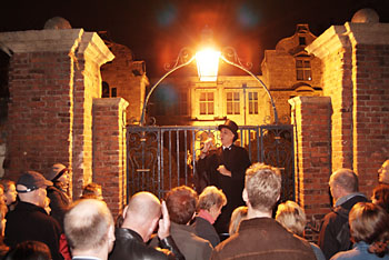Ghost walk guide entetains tour.